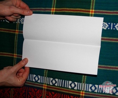 Необходимо взять бумагу форматом А4 и сложить пополам по длине листа. Затем его расправляем и приступаем к углам