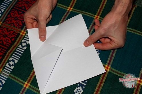 Теперь снова надо сложить уголок. Но сделать это требуется таким способом, чтобы остался маленький треугольничек.