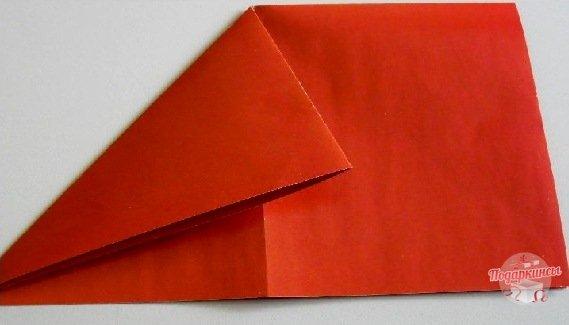 У согнутого таким образом листа следует сложить углы так, чтобы сгибы образовались от середины к нижним уголочкам.