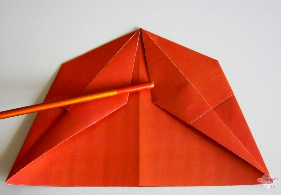 Сгибаем лист по диагонали к центру.